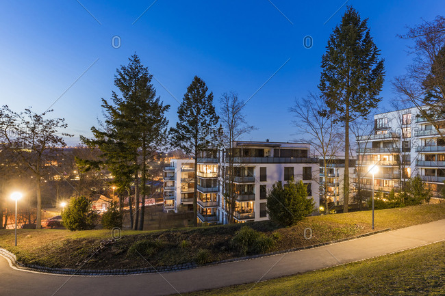 Germany- Baden-Wurttemberg- Stuttgart- Empty footpath in public park at dusk with modern apartments in background
