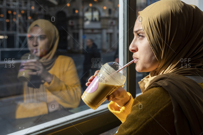 Portrait of pensive young woman drinking smoothie in a cafe