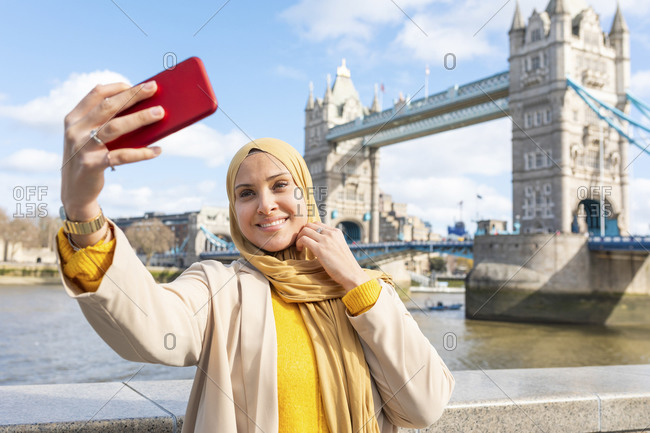 Portrait of smiling young woman taking selfie with smartphone in front of Tower Bridge- London- UK