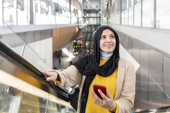Portrait of a smiling young woman wearing hijab standing on escalator