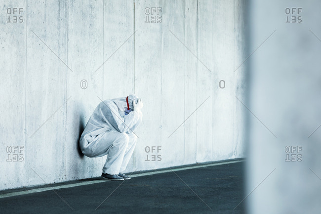 Despaired man wearing protective clothing leaning against concrete wall