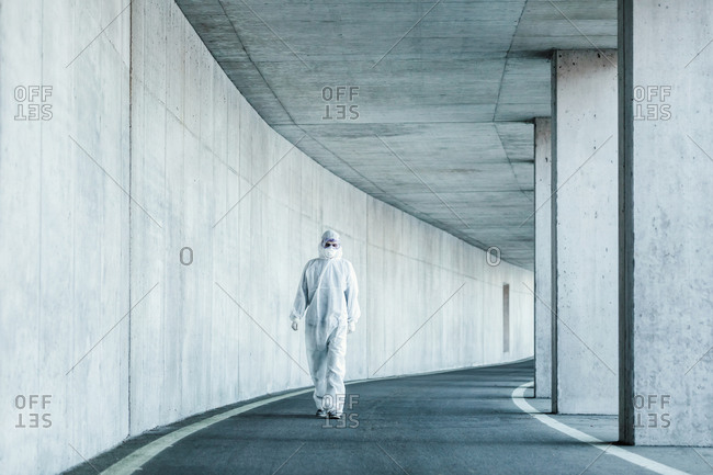 Man wearing protective clothing walking in a tunnel