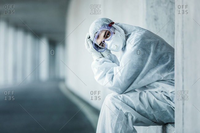 Portrait of a man wearing protective clothing sitting in a niche of a concrete wall in a tunnel