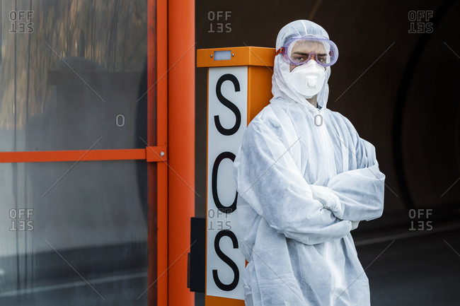 Portrait of man wearing protective clothing leaning against SOS telephone