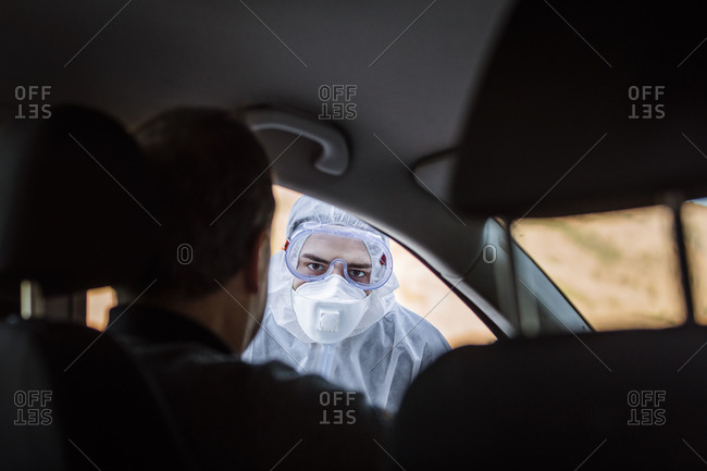 Man wearing protective clothing controlling senior man in car