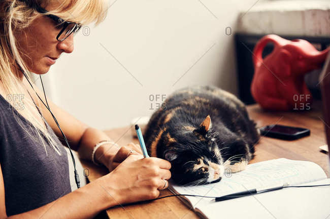 Woman writing note on desk with cat lying on notebook