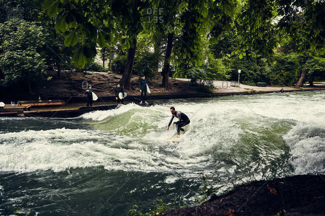 Munich, Germany - July 22, 2017: Surfer riding the current in the Eisbach River