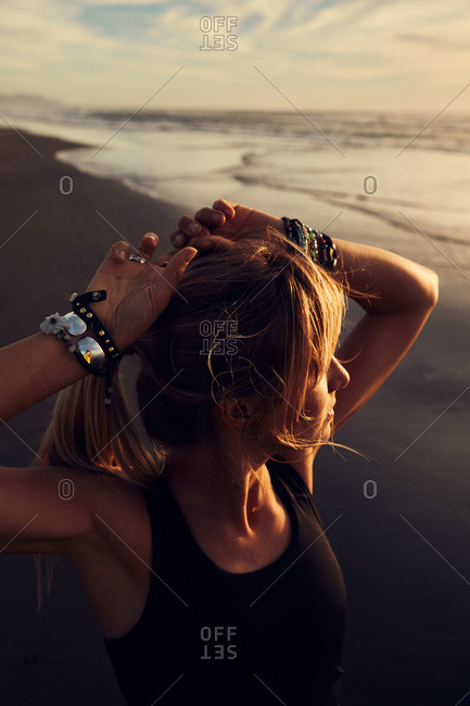 Blonde woman on a beach looking out at the sunset