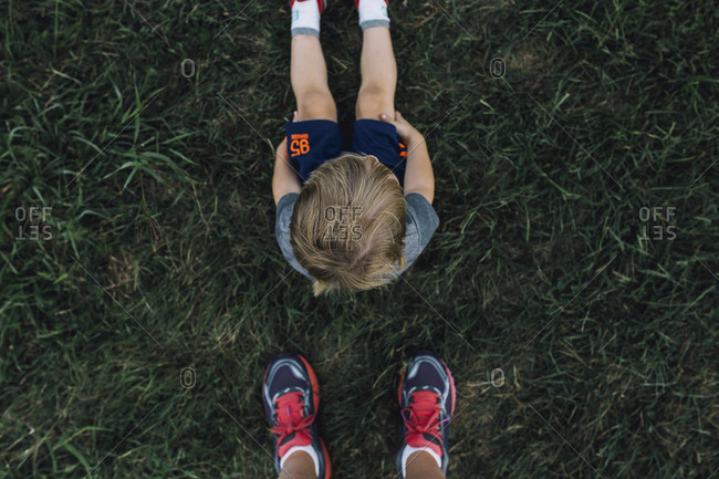 Overhead view of a toddler boy sitting in the grass