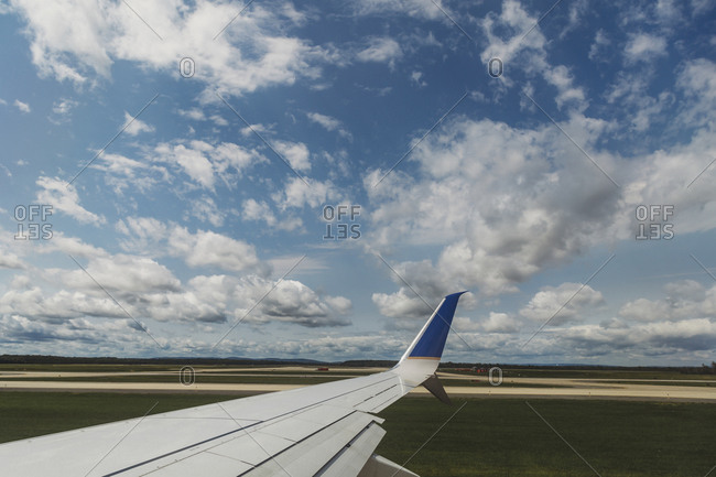 View of the wing of an airplane under cloudy sky while on the runway