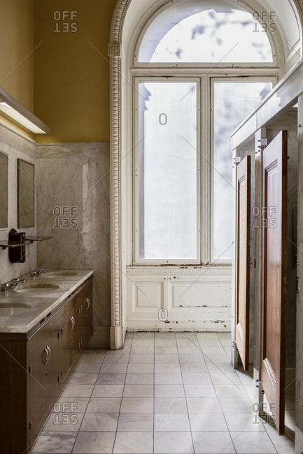 Interior of an old bathroom with large arched window and marble sinks