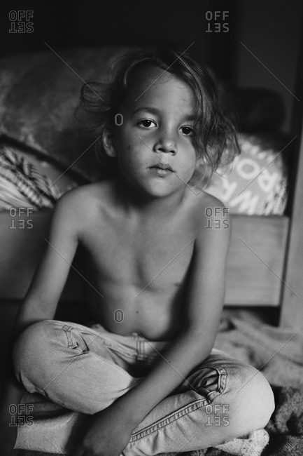 Young boy sitting shirtless in black and white