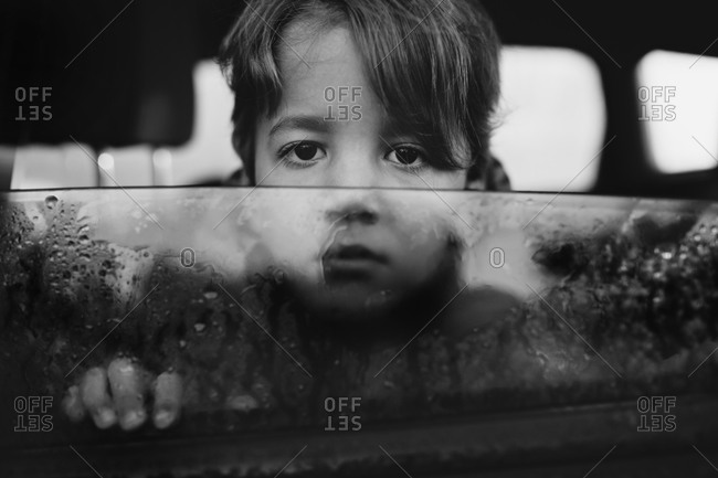 Young boy looking out wet car window with sad expression