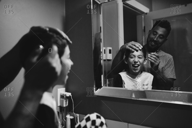 Father giving son a haircut in the bathroom