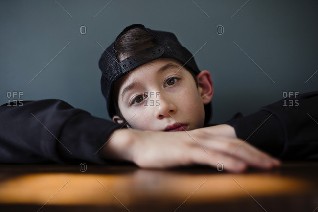 Boy wearing black baseball cap and gazing with a serious look on his face