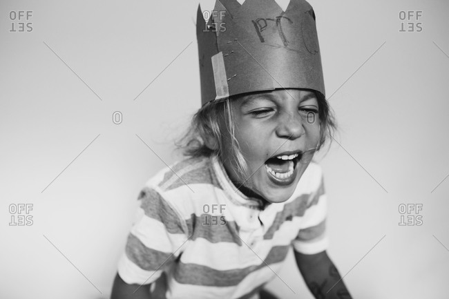Happy young boy laughing and wearing a prince crown