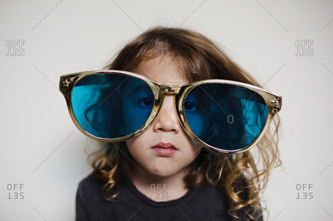 Boy with long curly hair wearing goofy large gold glasses