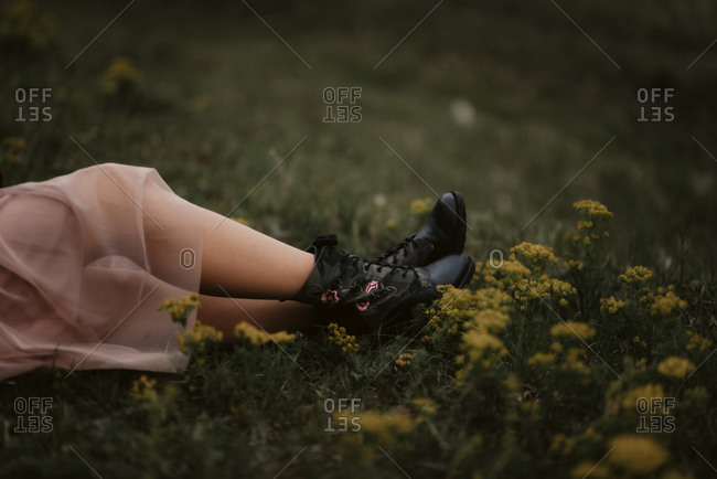 Woman\'s feet wearing black boots with pink flowers in a field
