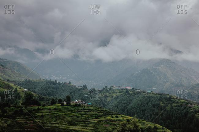 Green mountainside under dense clouds in Rohru, Shimla, Himachal Pradesh