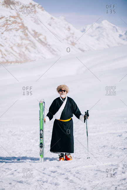 Spiti, Himachal Pradesh, India - April 2, 2019: Man standing on snowy hill holding skis and poles