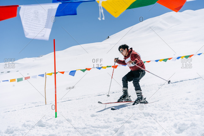 Spiti, Himachal Pradesh, India - April 1, 2019: Man skiing down snowy hill with Tibetan prayer flags