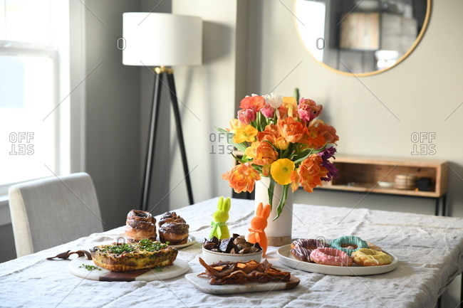 Breakfast foods and flowers on table for Easter brunch