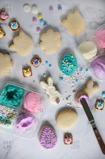 Easter cookies being decorated on white marble surface