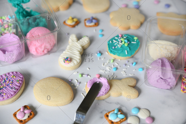 Close up of Easter cookies being decorated on white marble surface