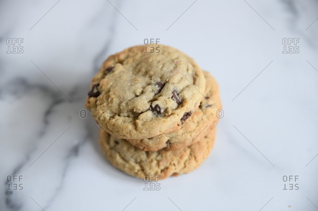 Small stack of chocolate chip cookies on white marble surface
