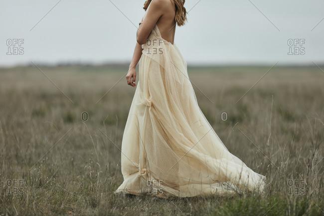 Woman walking though field wearing shear flowy dress