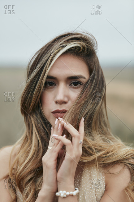 Close up portrait of a beautiful woman touching her hair