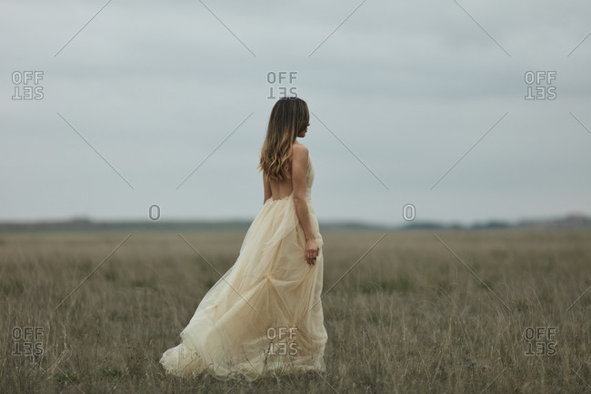 Woman with long hair walking though field wearing shear flowy dress