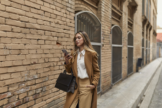 Businesswoman walking down city street looking at cell phone