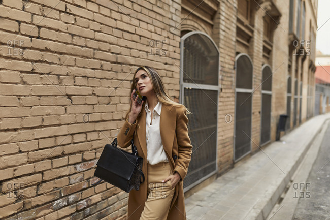 Businesswoman walking down city street talking on cell phone
