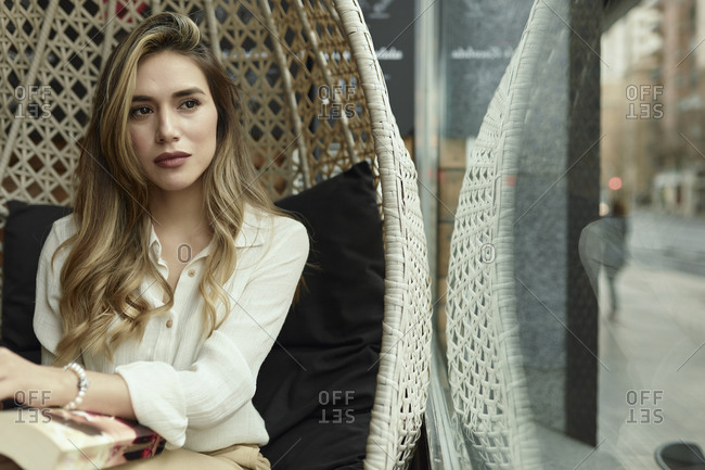 Businesswoman sitting in rattan chair at a caf��?