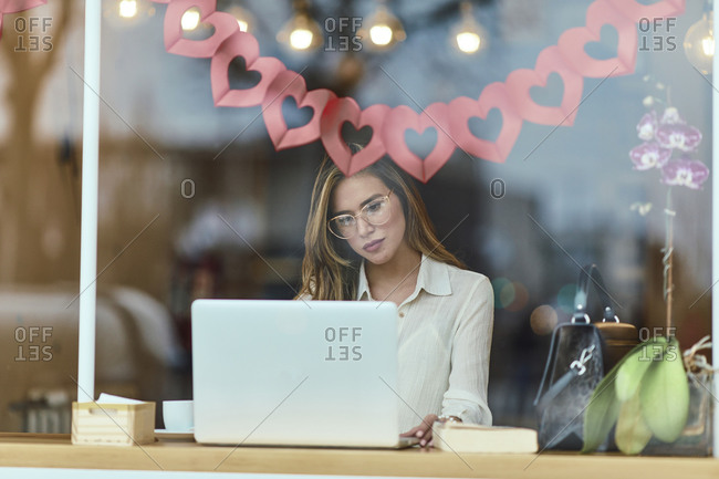View through window of a businesswoman sitting at a cafe using laptop