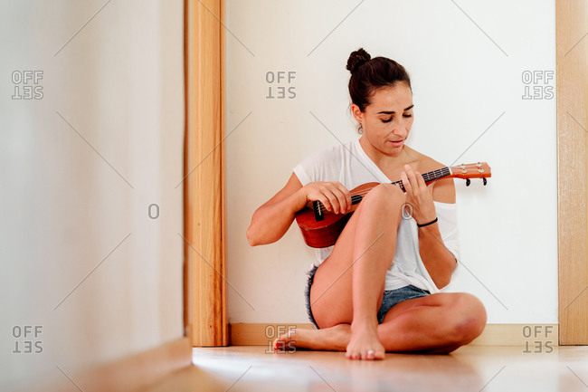The woman sitting on the floor of the house playing the ukulele