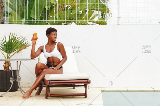 Portrait of a beautiful African-American woman with short hair and in a bikini sitting by a pool drinking a soda.