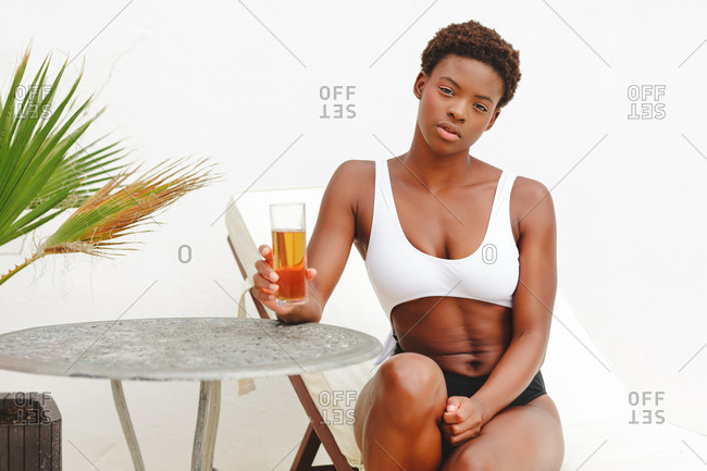 Portrait of a beautiful African-American woman with short hair and in a bikini, sitting and having a soda.