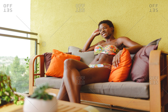 Young African-american woman in a bikini, sitting on the couch on the terrace