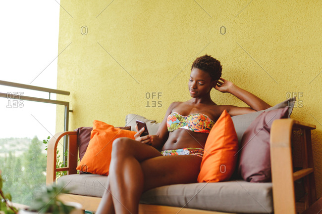 Young African-American woman in a bikini, using her phone while resting on the couch on the terrace