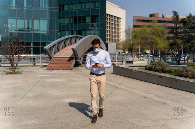 Young caucasian man walking in business district wearing face mask against air pollution and coronavirus, he is using his cellphone.