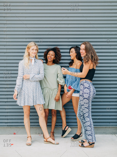 Four happy diverse women standing by a grey wall outdoors