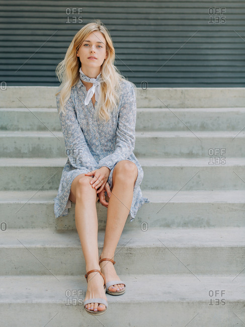 A white woman with blonde hair sitting on concrete stairs outside