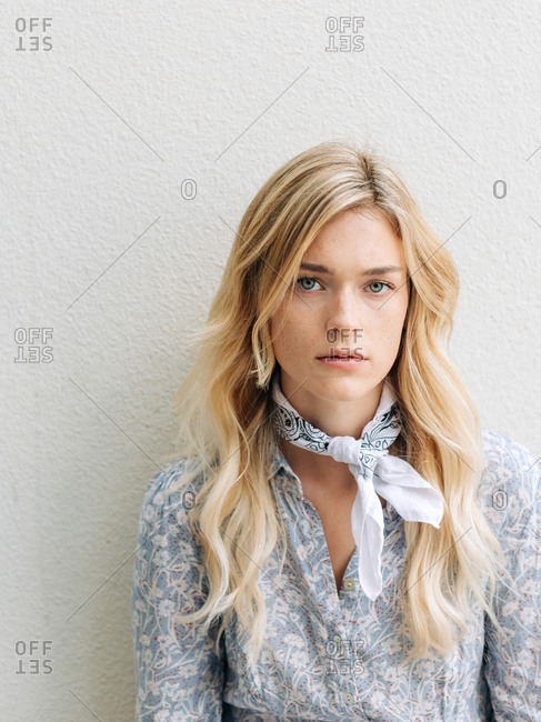 A white woman with blonde hair against a white wall with serious face