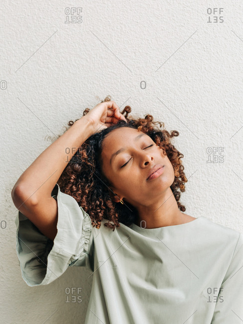 A black woman leaning against white wall with eyes closed and hand in hair