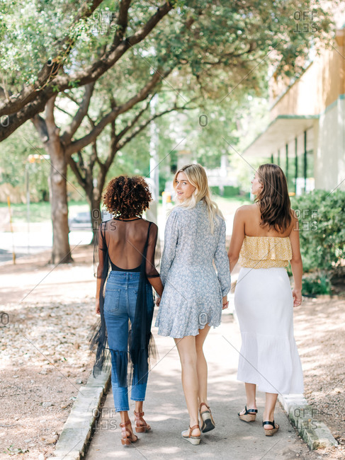 Three diverse women walking down a sidewalk and one looking back and smiling