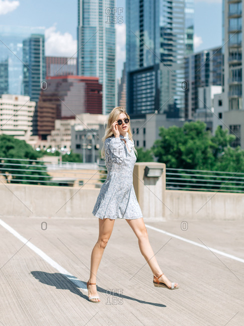 White woman on rooftop with skyline in the background