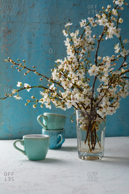 Cherry blossom twigs and coffee mugs on white table