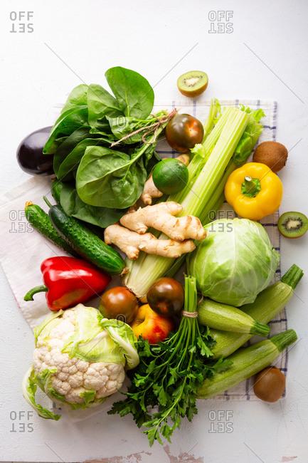 Fresh organic vegetables on linen cloth on white table